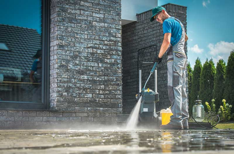 Man using pressure washer after following tips