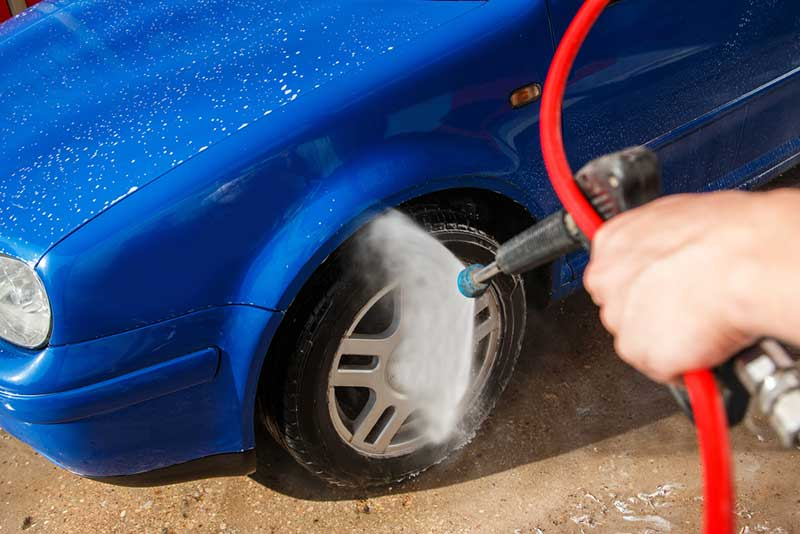 Pressure washer being used on a tire